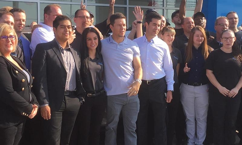 Posing with staff of the dealership at the opening day of Mark Wahlberg Chevrolet