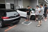 Scirocco owners admire the quad pipe-equipped rear end of the black demo car.
